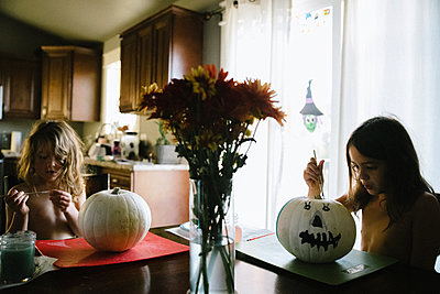 Two sisters painting pumpkins for Halloween at the kitchen table - p1166m2269342 by Cavan Images