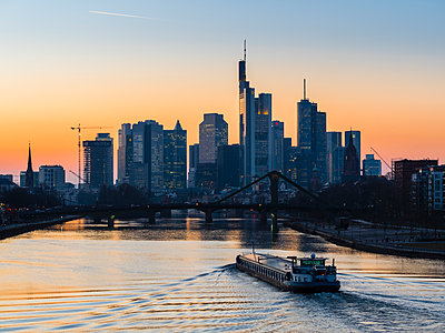 Germany, Frankfurt, view to skyline with Floesserbruecke and Main River in the foreground at morning twilight - p300m1356288 by Martin Moxter