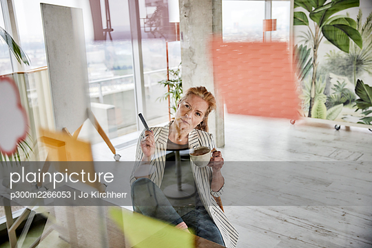 Female entrepreneur holding coffee cup while doing business plan seen through glass wall at office - p300m2266053 by Jo Kirchherr