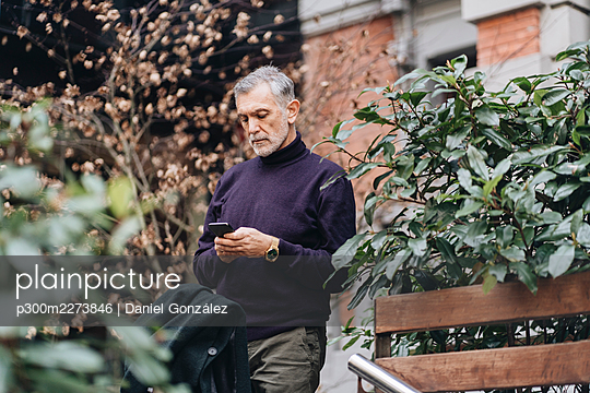 Mature man using mobile phone while standing by plant - p300m2273846 by Daniel González