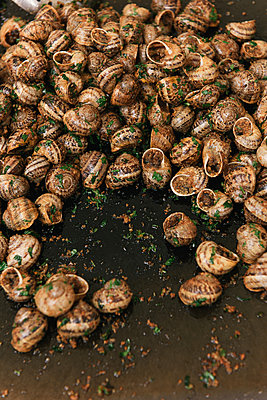 Gridle roasted escargot and herbs at a market in France - p1166m2191890 by Cavan Images