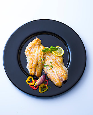 Redfish fillet on black plate garnished with herbs - p300m2083989 by Pro Pix