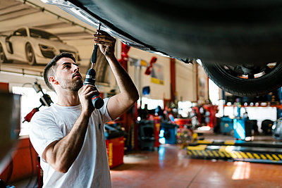 Young mechanic repairing car with work tool in auto repair shop - p300m2220693 by Ezequiel Giménez
