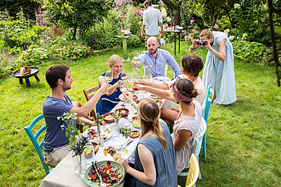 Friends on garden party toasting white wine - p788m1165321 by Lisa Krechting
