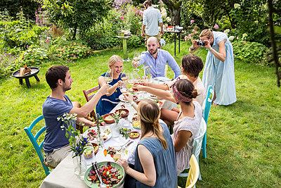 Freunde auf Gartenparty stoßen mit Weißwein an  - p788m1165321 von Lisa Krechting