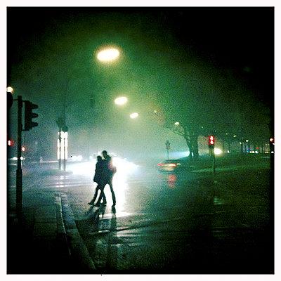 Paar nachts im Regen auf einer Straße - p979m1146572 von Werner Gritzbach
