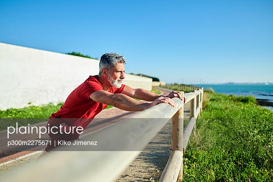 Man stretching on railing during sunny day - p300m2275671 by Kiko Jimenez