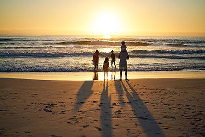 Family wading in summer ocean surf at sunset - p1023m2200819 by Trevor Adeline