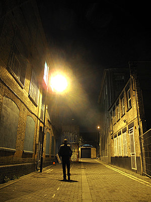 Silhouetted man walking down East End alley - p1072m829409 by Neville Mountford-Hoare