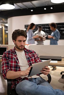 Bearded guy using tablet in coworking space - p1166m2234901 by Cavan Images
