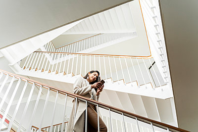 Young woman with smartphone walking down stairs in staircase - p300m2166197 by VITTA GALLERY