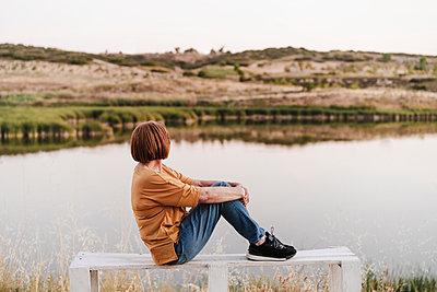 Senior woman looking at mountains while sitting on bench near lake - p300m2293394 by Eva Blanco