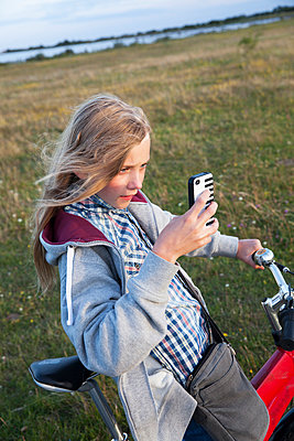 Girl on bike taking picture with her cell phone, Sweden - p312m927342f by Lena Granefelt