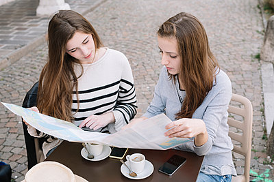 Girlfriends reading street map at cafe - p429m2023138 by Alberto Bogo