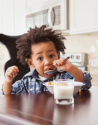 Mixed race boy eating at table - p555m1464117 by Mike Kemp
