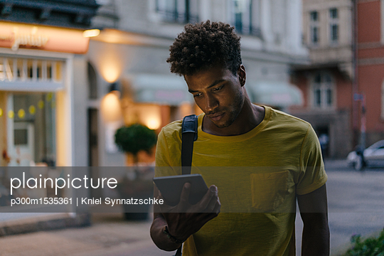 Man looking at phablet in the city at dusk - p300m1535361 by Kniel Synnatzschke