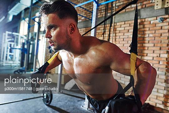 Man doing exercise with suspension straps in gym - p300m1581748 von gpointstudio
