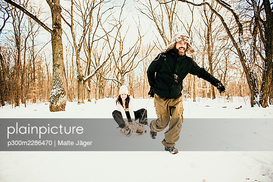Boyfriend running while pulling sled with girlfriend sitting on it at forest - p300m2286470 by Malte Jäger