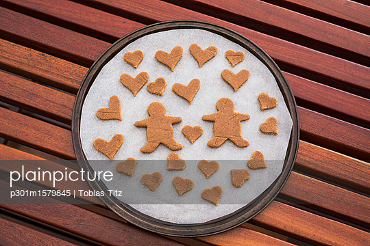 Gingerbread couple surrounded by hearts in baking sheet on table - p301m1579845 by Tobias Titz