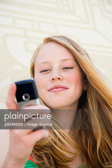 A teenage girl using a cell phone - p9248420f by Image Source