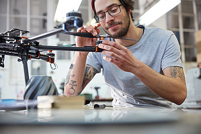 Male designer with tattoos assembling drone in workshop - p1023m1486408 by Agnieszka Olek