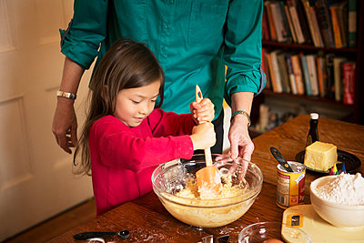 Midsection of grandmother with girl preparing cookies at home during Christmas - p1166m1038158f by Cavan Images