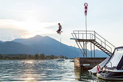 Austria, Sankt Wolfgang, man jumping from platform into lake - p300m1189329 by JLPfeifer