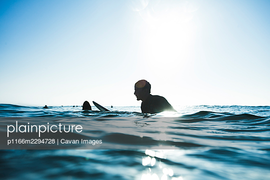 surfer waiting for wave, sitting on board, blue - p1166m2294728 by Cavan Images