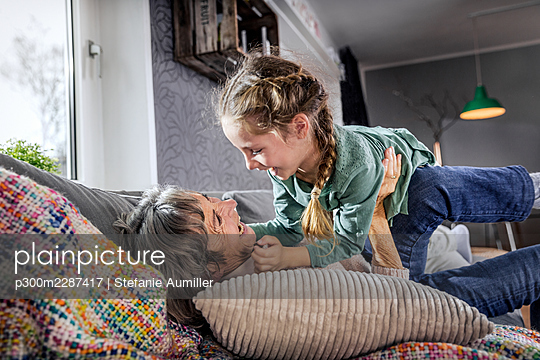 Grandmother playing with granddaughter while lying on sofa at home - p300m2287417 by Stefanie Aumiller