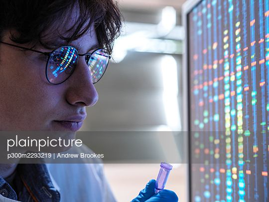 Male scientist checking DNA on computer at laboratory - p300m2293219 by Andrew Brookes