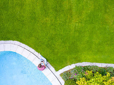 Man sitting at poolside with remote control navigating drone - p300m2005472 von Michael Malorny