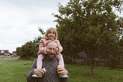 Father carrying his little daughter on shoulders - p300m2042378 by Katharina Mikhrin