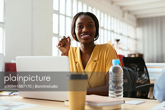 Portrait of smiling young woman at desk in office - p300m1587170 von Bonninstudio