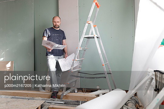Wickede; NRW, Deutschland. Ein Mann in mittleren Alter in einem renovierten Zimmer schaut Baupläne an - p300m2167205 von Katharina Mikhrin
