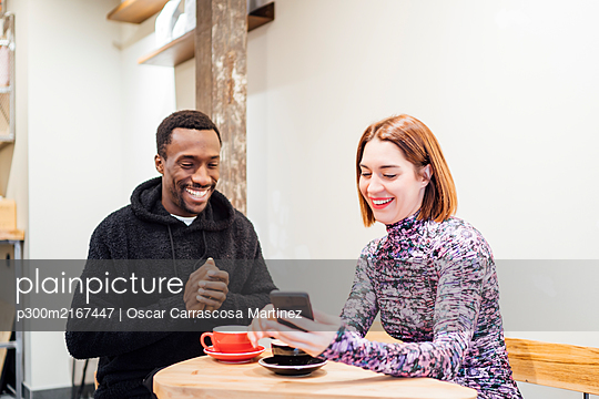Smiling man and woman with cell phone in a cafe - p300m2167447 by Oscar Carrascosa Martinez