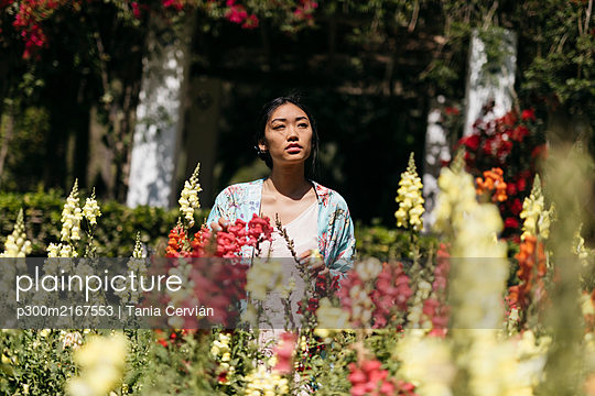 Beautiful young woman surrounded by flowers in a public garden in spring - p300m2167553 by Tania Cervián