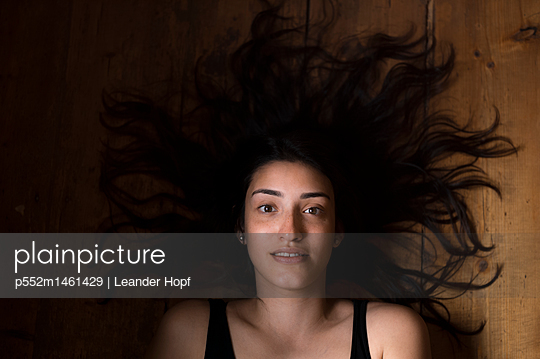 Portrait of young woman with long hair - p552m1461429 by Leander Hopf