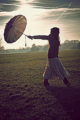 Woman walking field holding umbrella behind - p1047m789488 by Sally Mundy