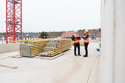 Two men wearing safety vests talking on construction site - p300m1459801 by Daniel Ingold