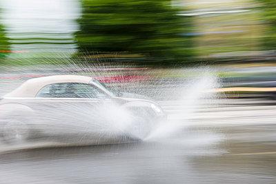 Car splashing water on road - p312m1103626f by Mikael Svensson