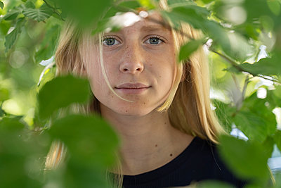 Portrait of teenage girl behind branches - p352m2120548 by Andreas Ulvdell