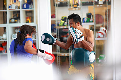 Mature woman practicing boxing with male trainer in gym - p429m1547754 by Peter Muller
