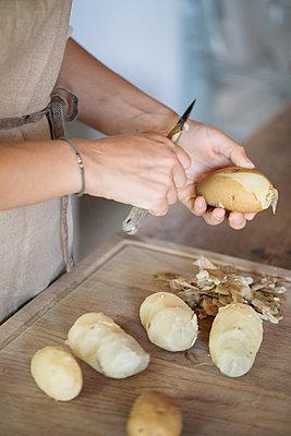 Woman peeling potatoes for gnocchi - p429m2035652 by Alberto Bogo