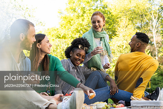 Smiling young friends sitting together in public park - p623m2294737 by Frederic Cirou