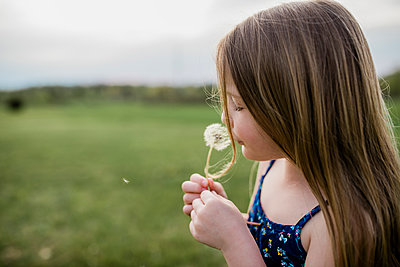 Side view of girl with dandelion flower on grassy field - p1166m1568996 by Cavan Images