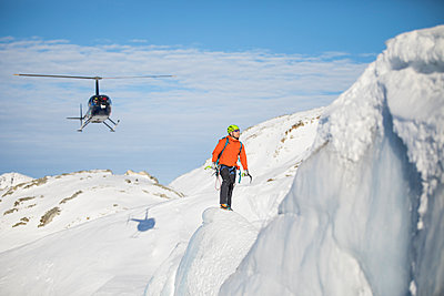 Ice climber looks at his next challenge, helicopter behind. - p1166m2124314 by Cavan Images