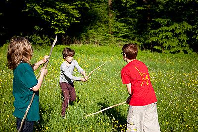 Jungen beim Stockkampf im Park - p1195m1138133 von Kathrin Brunnhofer