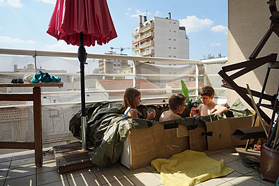 Children playing in a self made swimming pool on their balcony - p1610m2221798 by myriam tirler