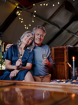 Portrait of senior couple having a candlelight dinner on a boat in boathouse - p300m2154964 von Gustafsson