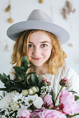 Portrait of woman holding bunch of flowers, looking at camera smiling - p429m1569688 by Lena Mirisola